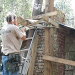 """Craftsman Jeff Penuel secures timber """"strong-backs"""" to the dilapidated chimney prior to """"righting"""" and stabilizing it. Jeff's knowledge of Cracker-style carpentry and his generous donation of his time were invaluable to the restoration."""